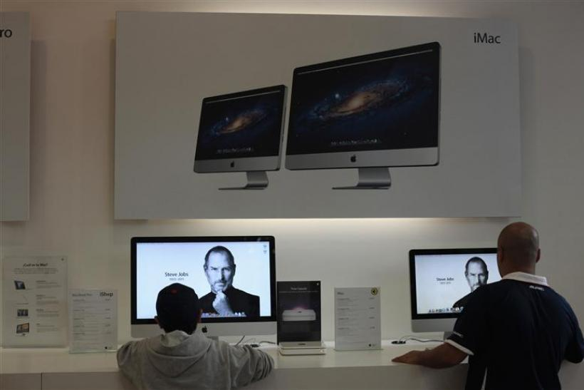 Two people look at the image of Steve Jobs on Apple computers inside the iShop in Guatemala City