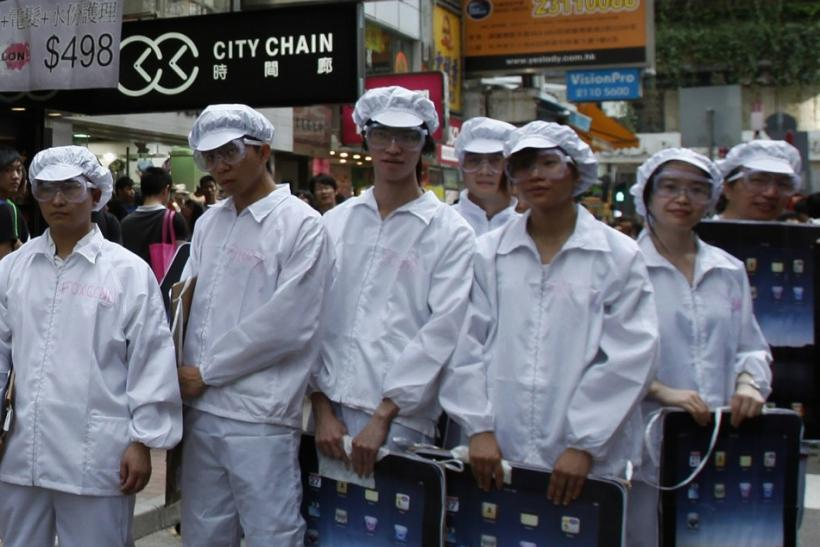 "Local and mainland Chinese university students dress as Foxconn workers during a rally in Hong Kong in May, demonstrating against the ""dire"" working conditions of workers from Foxconn and Apple."