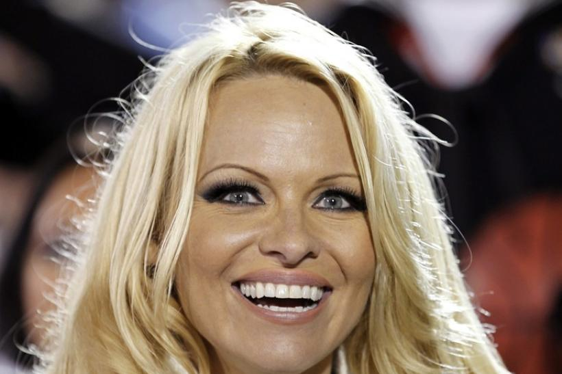 Pamela Anderson watches the NCAA Carrier Classic men's college basketball game between Michigan State Spartans and the North Carolina Tar Heels in Coronado