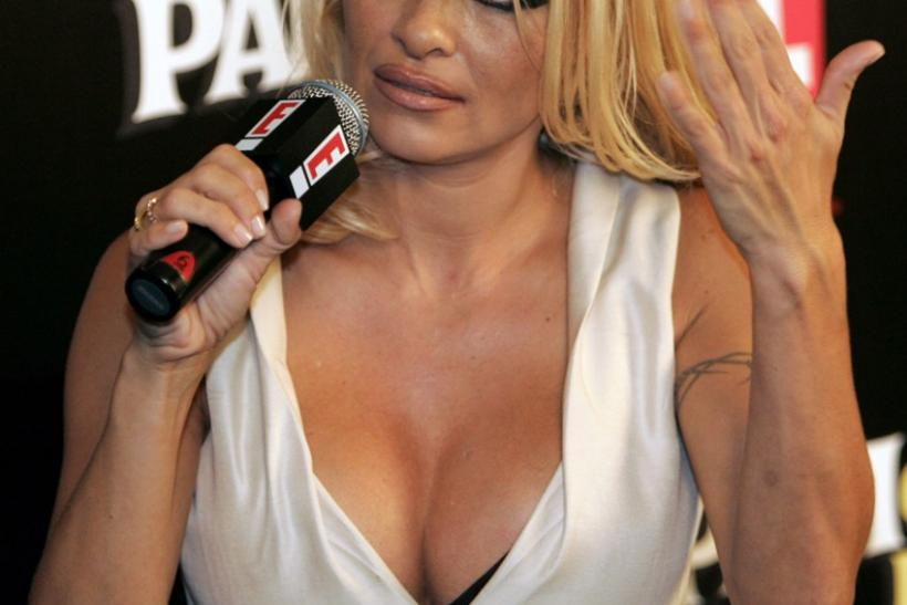 U.S actress Pamela Anderson fans her face as she reacts to the heat during her Sydney news conference