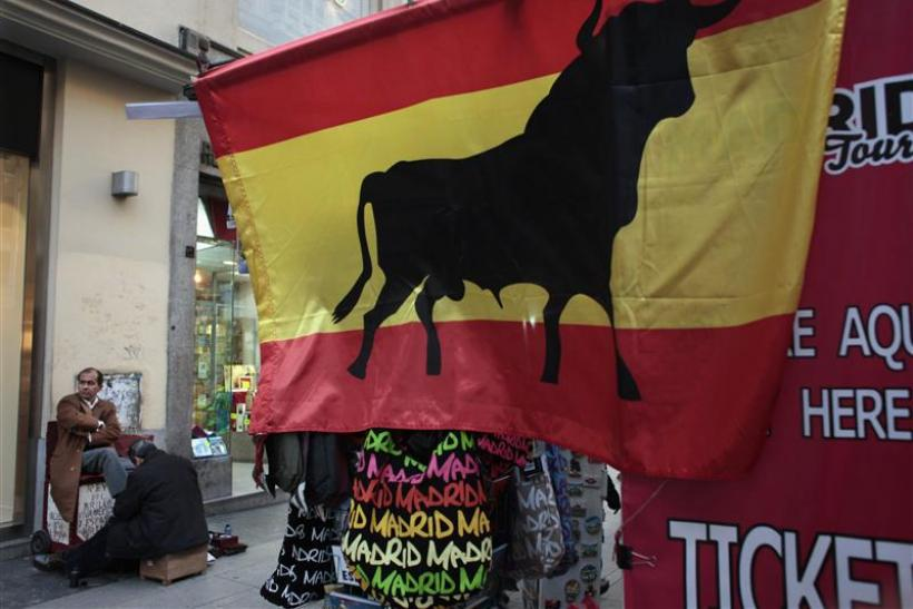 A man gets a shoeshine next to a kiosk displaying a Spanish flag with a bull on it in downtown Madrid