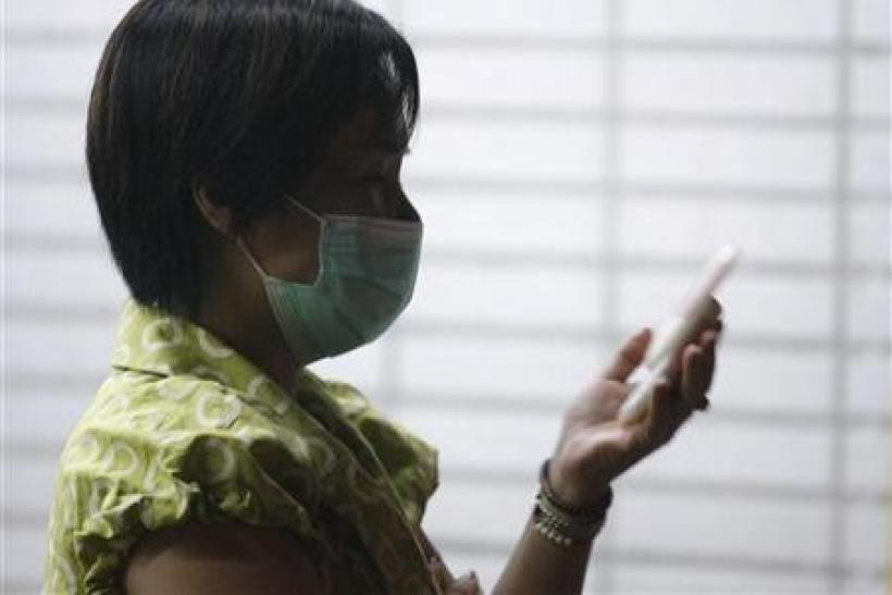 A woman wearing a medical mask uses her mobile phone outside a hospital in Taipei May 21, 2009.