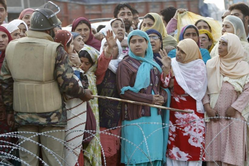 A security personnel directs with a baton at the relatives of Kashmiri Hajj pilgrims, to not cross the barbed wires before the pilgrims' departure in Srinagar
