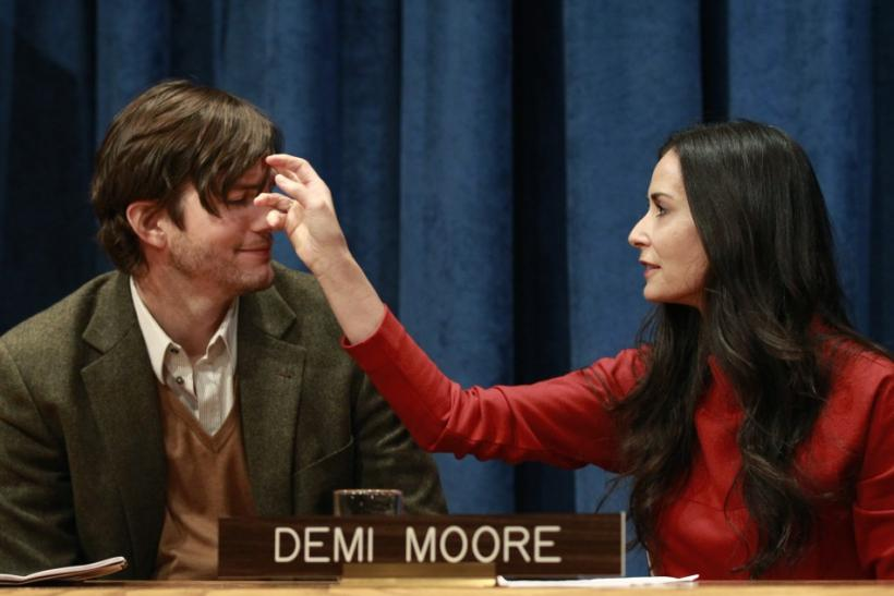 Actress Demi Moore brushes her husband, Ashton Kutcher's hair, prior to a news conference at the United Nations Headquarters in New York
