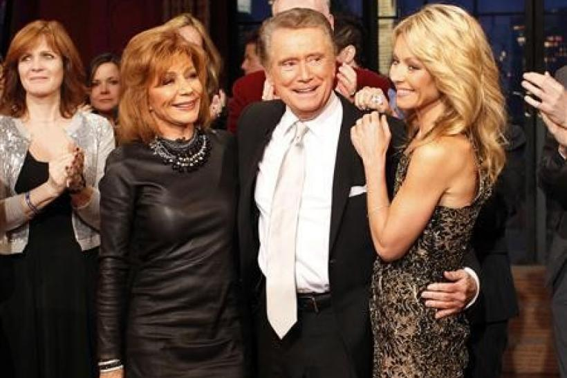 """Television host Regis Philbin (C) says goodbye with his wife Joy Philbin (L) and co-host Kelly Ripa (R) during his final show of """"Live With Regis and Kelly"""" in New York"""