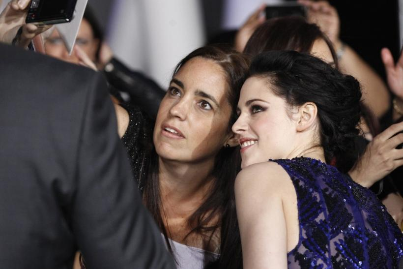 "Stewart poses with a fan at the premiere of ""The Twilight Saga: Breaking Dawn - Part 1"" in Los Angeles"