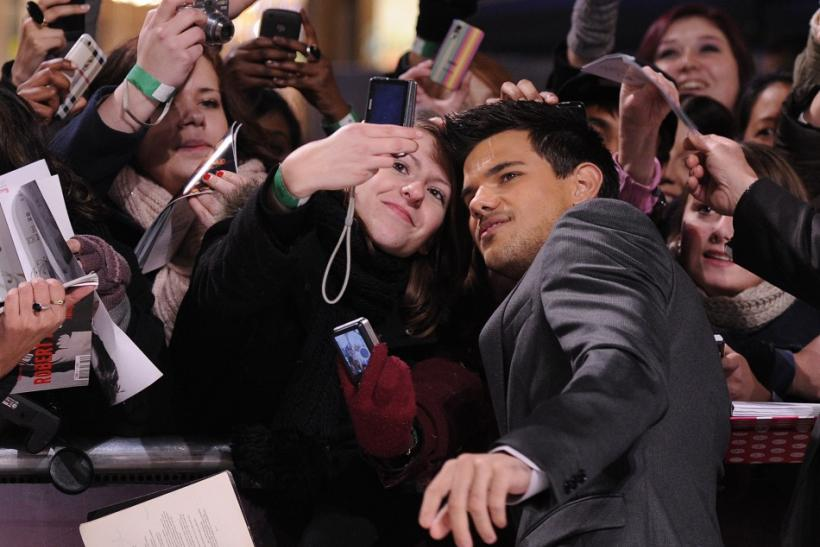 "Lautner poses with a fan at the premiere of ""The Twilight Saga: Breaking Dawn - Part 1"" in Los Angeles"