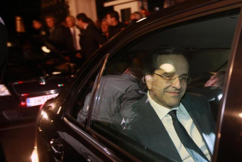 Antonis Samaras smiles as he leaves the presidential palace after a meeting with President Karolos Papoulias and Prime Minister George Papandreou in Athens