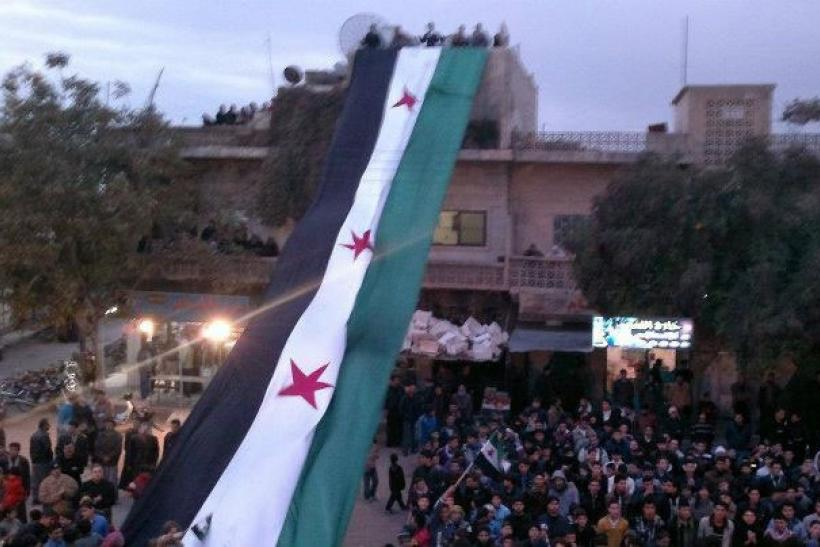 Demonstrators against Syria's President Bashar al-Assad display a large 1961-63 Syrian flag during a march after Friday prayers in Kafranbel near Adlb