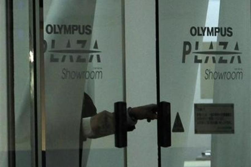 A man closes door of Olympus Corp's showroom in Tokyo November 10, 2011.