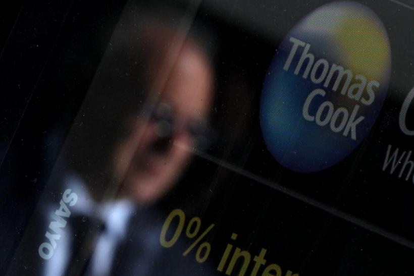 A pedestrian is reflected in the window of a branch of travel agent Thomas Cook in London