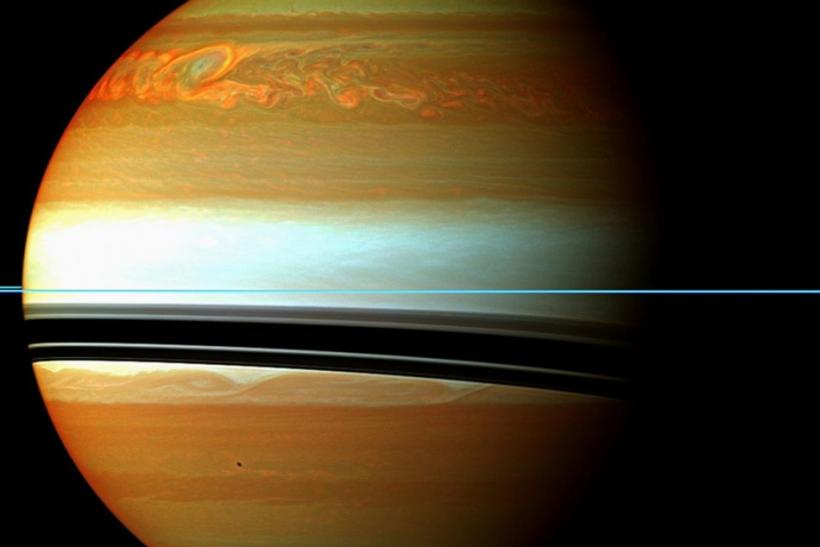 NASA handout image shows Saturn's atmosphere and its rings in a false color composite made from 12 images, captured on January 12, 2011. The mosaic shows the tail of Saturn's huge northern storm
