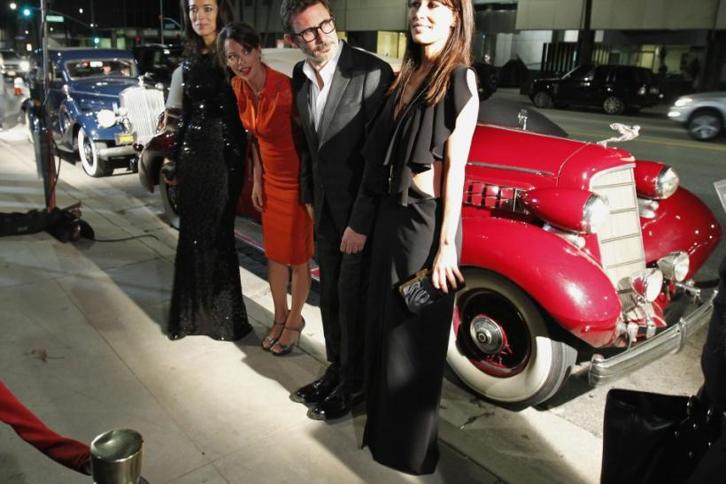 French director Michel Hazanavicius (2nd R) and actress Berenice Bejo (C) pose with the granddaughters of the late silent film star Charlie Chaplin, Carmen (L) and Dolores Chaplin (R), next to the vintage automobile they arrived in, at a special screening
