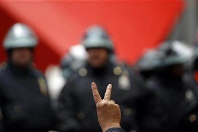 An Occupy Wall street protestor gestures in front of New York City Police inside Zuccotti Park as protests moved through the streets of lower Manhattan near the New York Stock Exchange during what organizers called a ''Day of Action''