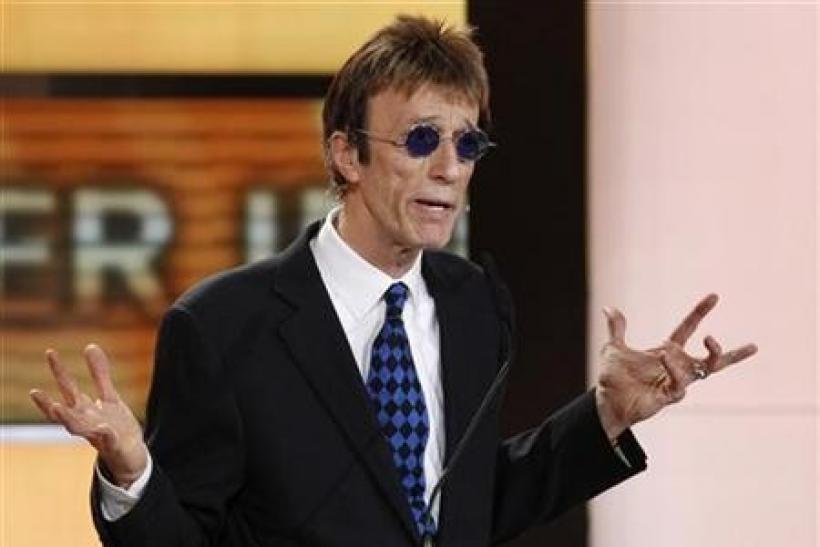 British musician Robin Gibb prepares to present U.S.actor John Travolta the award for best international actor during the 46th 'Goldene Kamera' (Golden Camera) awards ceremony at the Ullstein Auditorium in Berlin, February 5, 2011.