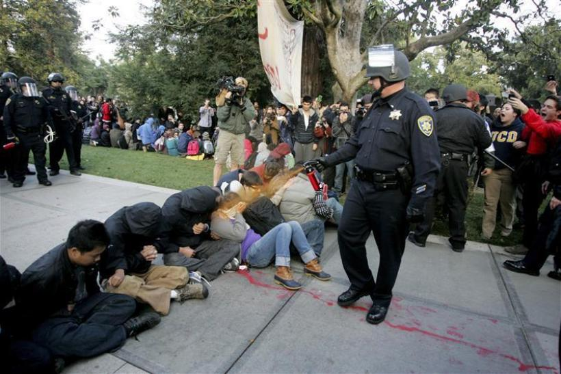 "A University of California Davis police officer pepper-sprays students during their sit-in at an ""Occupy UCD"" demonstration in Davis"