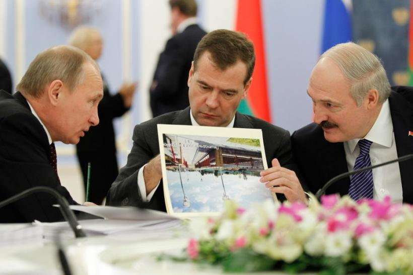 Russian PM Putin talks to Belarus' President Lukashenko as Russia's President Medvedev reads document during a meeting in the Gorki residence outside Moscow