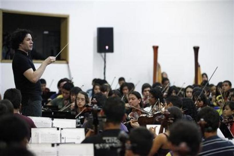 Simon Bolivar Youth Orchestra conductor Gustavo Dudamel leads the orchestra for a performance during a visit by conductor Daniel Barenboim at the venue of the National System of Children and Youth Orchestras of Venezuela in Caracas August 11, 2010.