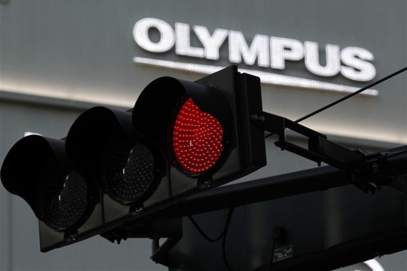A logo of Olympus Corp is seen behind a traffic signal outside of an electronic shop in Tokyo