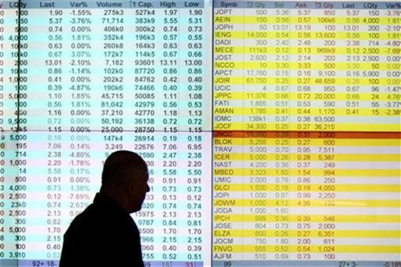 A dealer walks past an electronic board in the investors' gallery at the Amman Stock Exchange November 21, 2011.