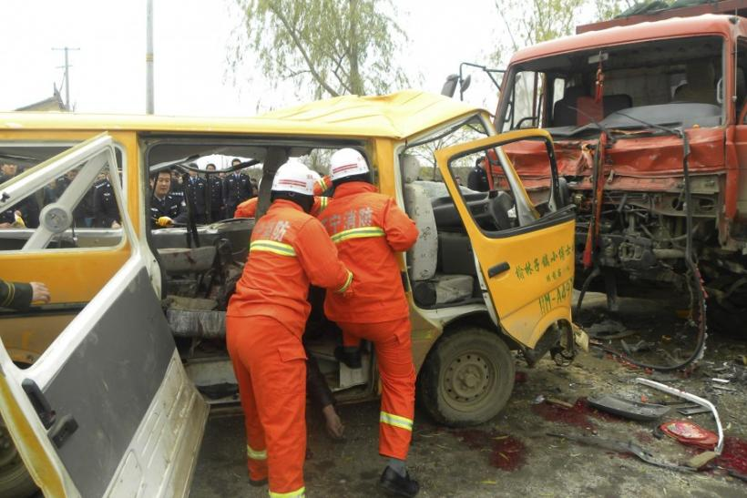 Rescuers pull a body out of a school bus after it collided with a truck at a traffic accident site in Yulinzi township of Zhengning county, Gansu province, November 16, 2011. Nineteen people, including 17 preschoolers and two adults, died in the head-on c