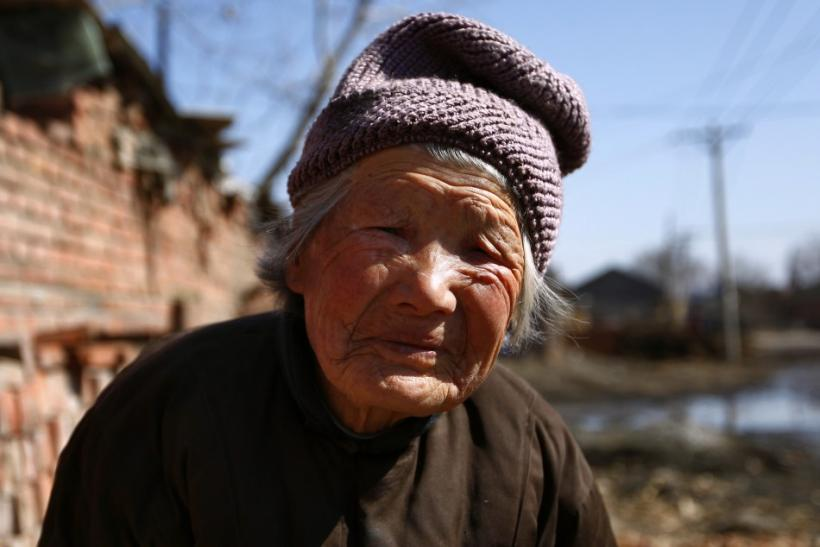 A 92-year-old woman takes a break from sorting corn cobs for selling to a local factory in an effort to make extra income in the village of Jianhua