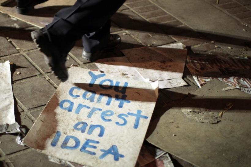 A Los Angeles police officer walks past a sign after the Occupy LA encampment was dismanted outside City Hall in Los Angeles