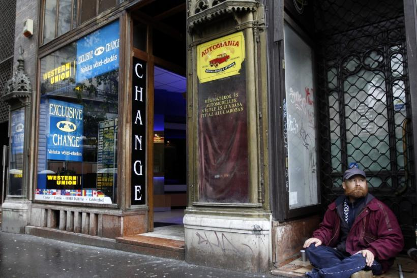 A homeless man begs for money next to a money changer in Budapest