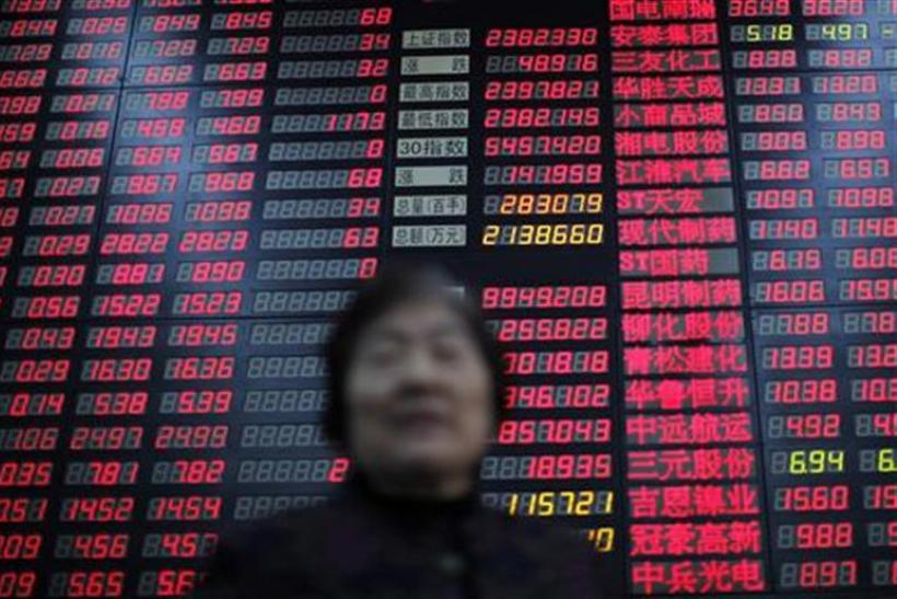 An investor stands in front of an electrical board showing stock information at a brokerage house in Shanghai