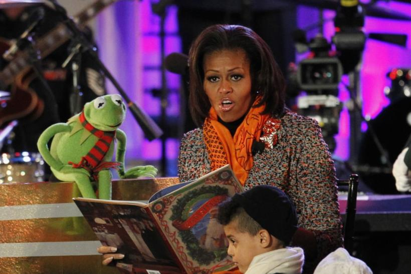 U.S. first lady Michelle Obama reads a Christmas story to children with the help of Kermit the Frog character, during the National Christmas Tree lighting ceremony in Washington