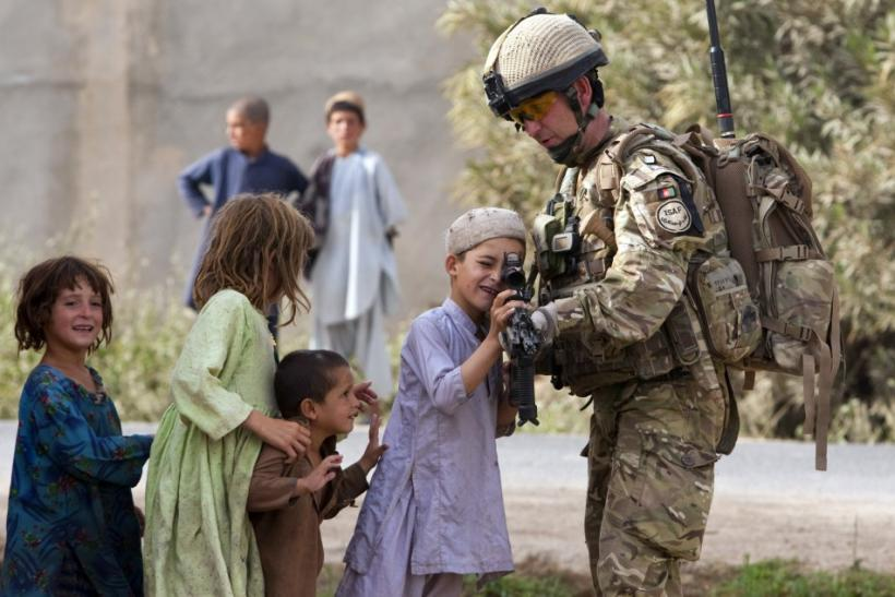 A British Army Major shows his rifle to Afghan children during a patrol outside Checkpoint Tander near Lashkar Gah in Helmand province