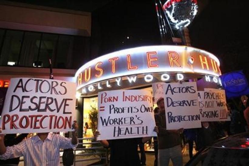 Activists hold signs during a rally in support of the use of condoms in the adult film industry in West Hollywood, California June 15, 2009.