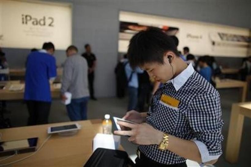 A man looks at an Apple iPad 2 at the company's new store in Nanjing Road, Shanghai