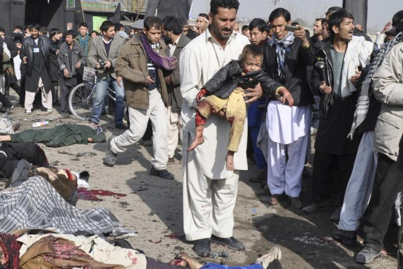A man carries a wounded boy after a suicide blast targeting a Shi'ite Muslim gathering in Kabul