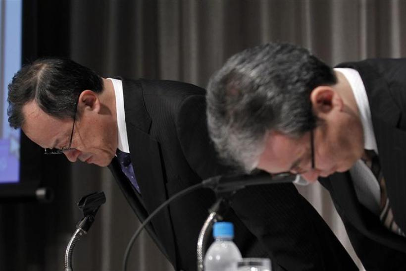 Olympus Corp President Takayama and accounting division's official Onishi bow at the start of a news conference in Tokyo