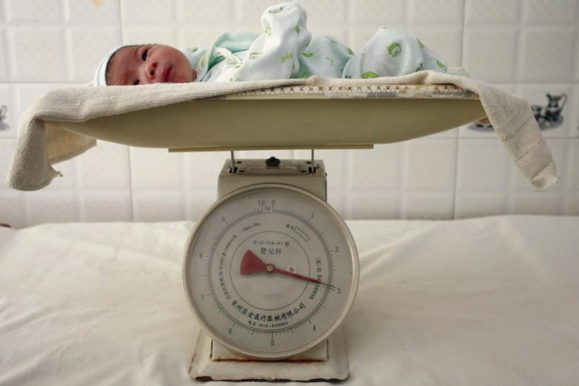 A newborn baby is put on a scale at a hospital in Suining