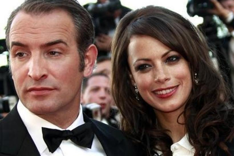 Cast members Jean Dujardin (L) and Berenice Bejo pose as they arrive on the red carpet for the screening of the film ''The Artist'' by director Michel Hazanavicius in competition at the 64th Cannes Film Festival