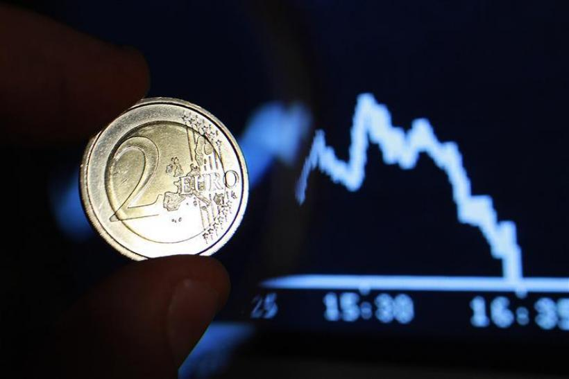 Photo illustration shows two euro coin through a magnifying glass near a picture of German share trading DAX index