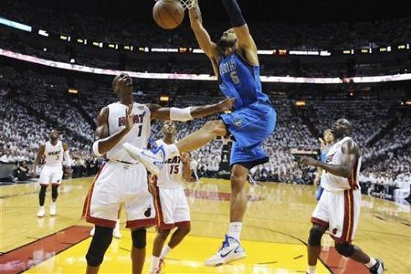 Dallas Mavericks center Tyson Chandler (6) dunks on Miami Heat forward Chris Bosh (1) in the first half during Game 6 of the NBA Finals series in Miami