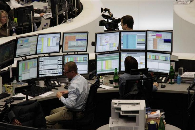 Traders are pictured at their desks at the Frankfurt stock exchange