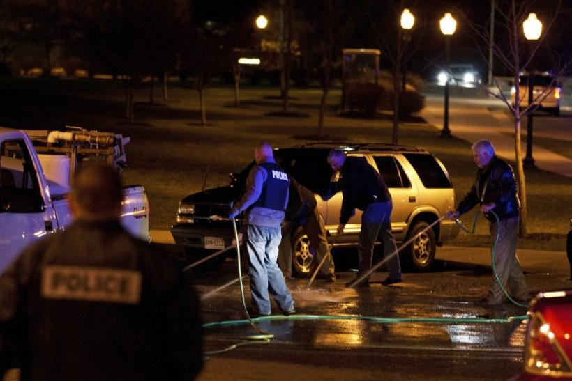 Law enforcement officers work to clean the road at the site where a Virginia Tech police officer was shot and killed at Virginia Tech University Blacksburg, Virginia