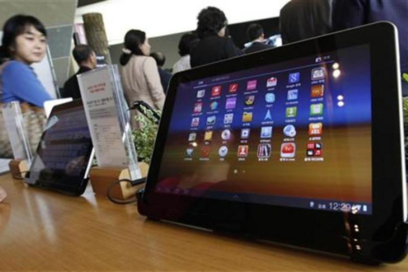 Visitors walk past Samsung Electronics' Galaxy Tab 10.1 tablets on display in Seoul