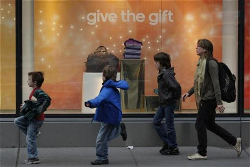 Children run past a storefront decorated for the holidays in New York