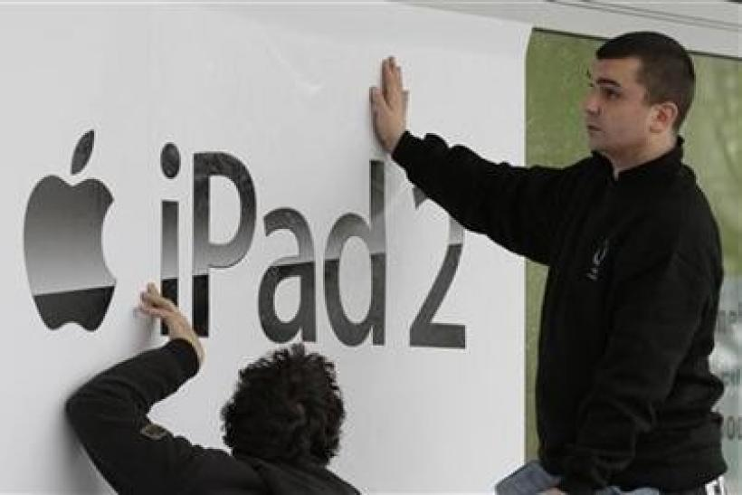 Workers stick-up a banner advertising the new iPad 2 at a computer store in Berlin
