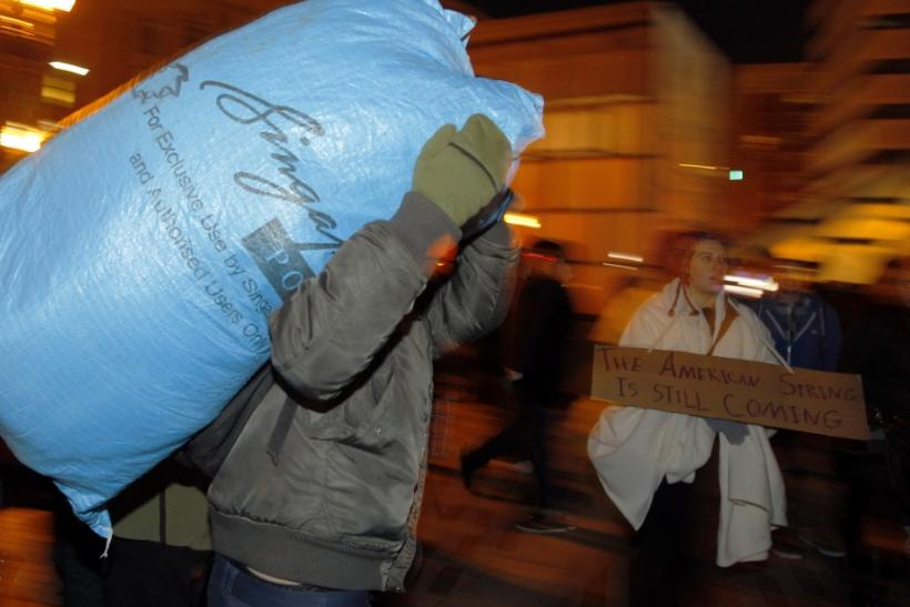An Occupy Boston protester carries away a bag of belongings before a midnight deadline set by Boston Mayor Tom Menino for the group to leave its encampment in the city on Thursday December 8, 2011.