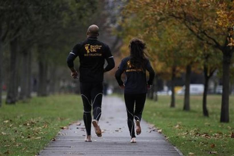 David Robinson (L) and Anna Toombs run barefoot in a park in south London December 1, 2011.