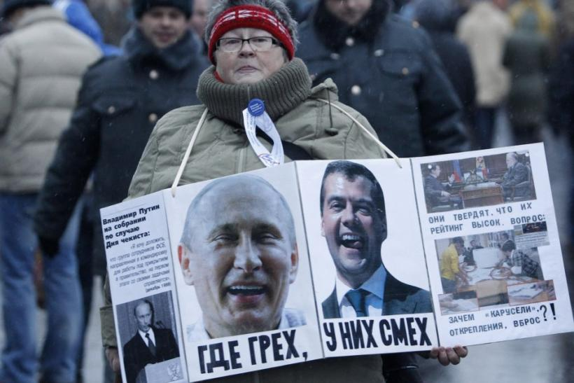 A woman carries a board displaying the portraits of Russia's President Dmitry Medvedev (R) and Prime Minister Vladimir Putin - December 10, 2011