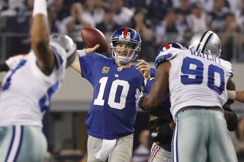New York quarterback Manning throws a pass as he is pressured by Dallas defensive tackle Ratliff in the first half of their NFL football game in Arlington, Texas