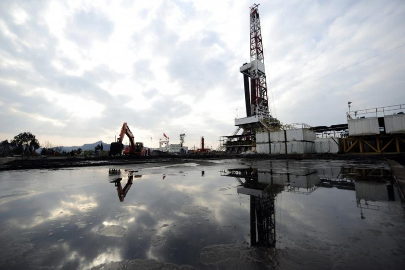 A natural gas appraisal well of Sinopec is seen behind a treatment pond of drilling waste in Langzhong county, Sichuan province March 1, 2011.