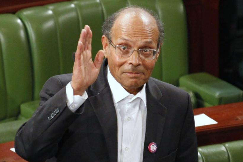 Former doctor and human rights campaigner Moncef Marzouki waves to the media at the constituent assembly in Tunis